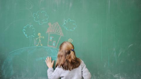 girl drawing buildings on a blackboard