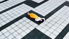 woman in yellow lying in the middle of a floor that looks like a puzzle